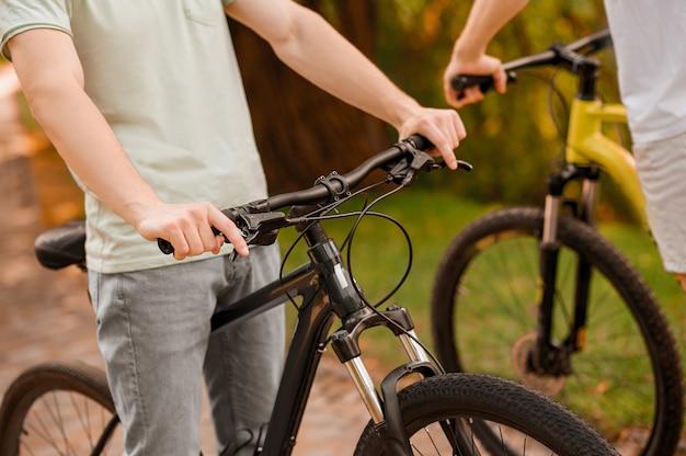 Przycięte zdjęcie dwóch dorosłych rowerzystów rekreacyjnych rasy kaukaskiej stojących razem na ścieżce rowerowej na świeżym powietrzu