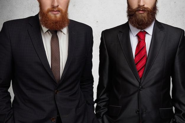 Przycięte zdjęcie dwóch kaukaskich brodatych przedsiębiorców ubranych w formalne garnitury, stojących z rękami w kieszeniach podczas spotkania biznesowego w biurze.