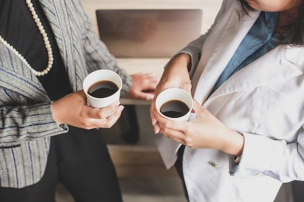 Przycięte zdjęcie dwóch kobiet biznesu wypić kawę w biurze