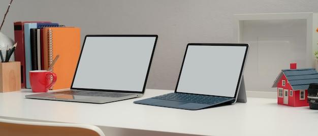 Przycięte zdjęcie dwóch laptopów pusty ekran na biurku z książkami i dekoracjami w pokoju biurowym w domu