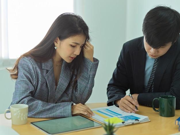 Przycięte zdjęcie dwóch przedsiębiorców pracujących razem nad dokumentami biznesowymi w sali konferencyjnej