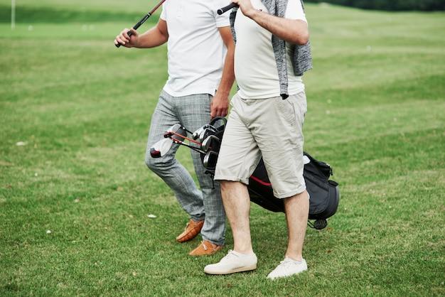 Przycięte zdjęcie dwóch przyjaciół na boisku sportowym ze sprzętem do golfa.
