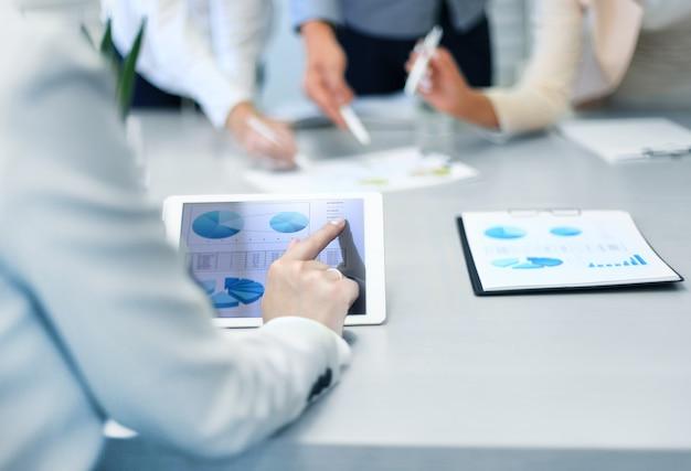 Przycięte zdjęcie grupy biznesmenów patrzących na wykresy na cyfrowych tabletach