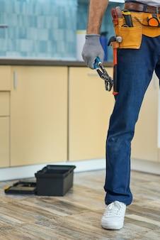 Przycięte zdjęcie hydraulika mechanika noszącego pasek narzędziowy trzymającego klucz do rur, przygotowującego się do