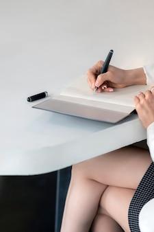 Przycięte zdjęcie kaukaski kobieta pisania na notebooku z piórem siedząc przy stole.