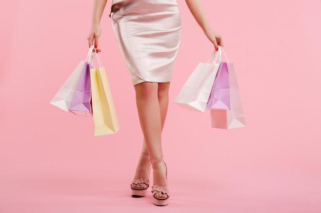 Przycięte zdjęcie kaukaski kobieta w sukience i butach letnich, trzymając kolorowe torby na zakupy, na białym tle nad różową ścianą