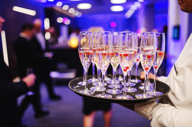 Przycięte zdjęcie kelnera trzymającego kieliszki szampana na tacy. wnętrze baru.