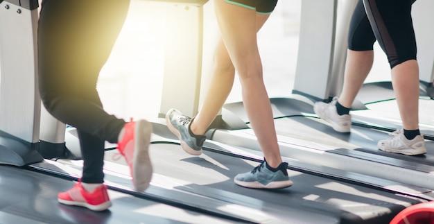 Przycięte zdjęcie kobiecych nóg w odzieży sportowej i trampkach na bieżni w siłowni przed oknem