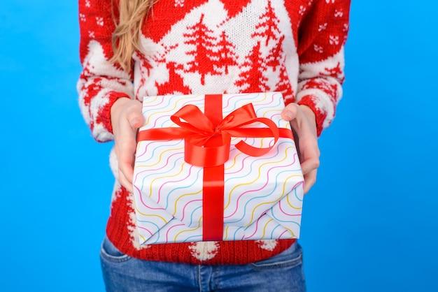 Przycięte zdjęcie kobiecych rąk trzymających duży prezent
