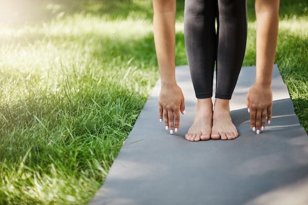 Przycięte zdjęcie kobiety robi pilates lub jogi lub ćwiczenia w parku. dłonie i stopy posadzone na macie do jogi.