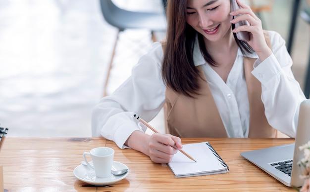 Przycięte zdjęcie kobiety strony pisania na notebooku podczas korzystania ze smartfona i pracy na biznes w biurze.