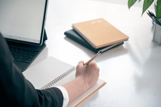Przycięte zdjęcie kobiety strony pisania na notebooku siedząc przy biurku.