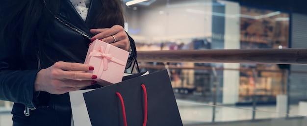 Przycięte zdjęcie kobiety trzymającej małe pudełko i oddanie go na zakupy z powrotem na tle centrum handlowego. koncepcja zakupu prezentów na wakacje z miejscem na kopię. pani po zrobieniu zakupów w sklepie