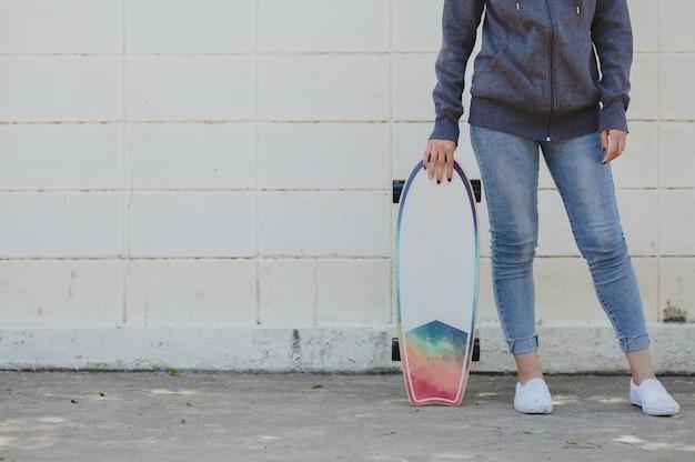 Przycięte zdjęcie kobiety w stroju casual z surfskate przed betonową ścianą. koncepcja aktywnego stylu życia