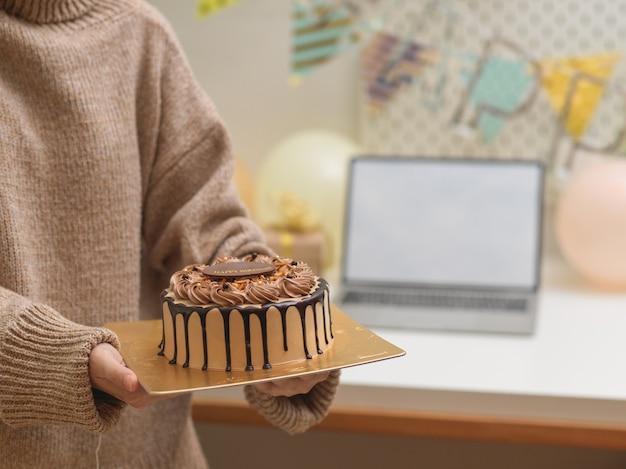 Przycięte zdjęcie kobiety w swetrze, trzymając w rękach tort urodzinowy