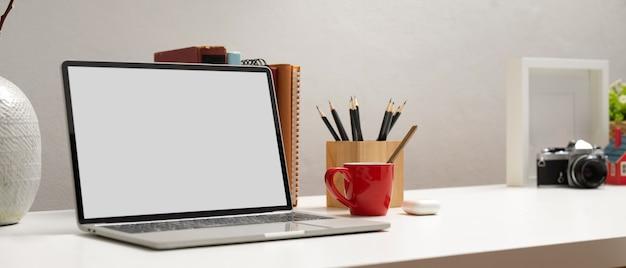 Przycięte zdjęcie komputera przenośnego ze ścieżką przycinającą na białym stole z papeterii i dekoracji w biurze domowym
