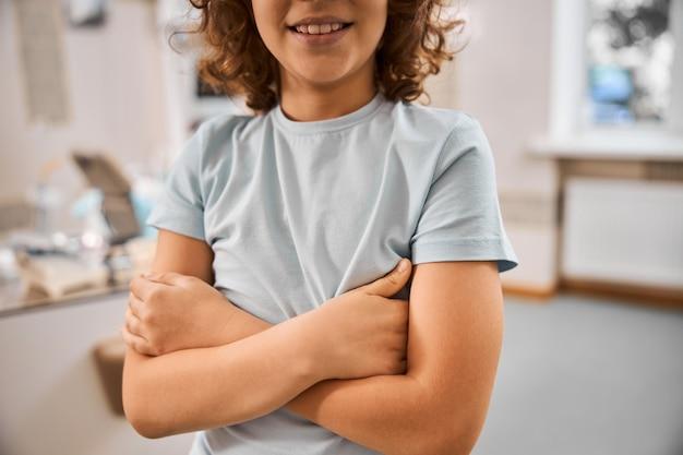 Przycięte zdjęcie kręconego uśmiechniętego chłopca w szarej koszuli stojącego ze skrzyżowanymi rękami w klinice dentystycznej