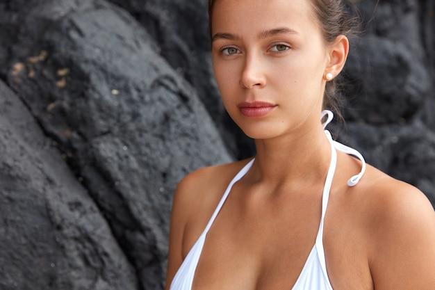 Przycięte zdjęcie ładnej kobiety ma poważny, pewny siebie wyraz twarzy, nosi białe bikini, wygląda wprost