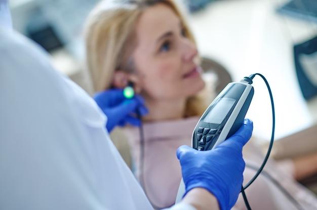 Przycięte zdjęcie lekarza w jednorazowych sterylnych rękawiczkach przeprowadzającego badanie audiometryczne na blond kobiecie