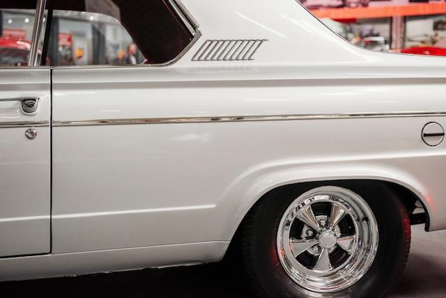 Przycięte zdjęcie lewej strony białego rzadkiego samochodu