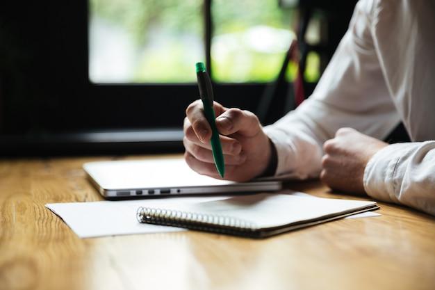 Przycięte zdjęcie mans ręki trzymającej zielony długopis, podczas robienia notatek