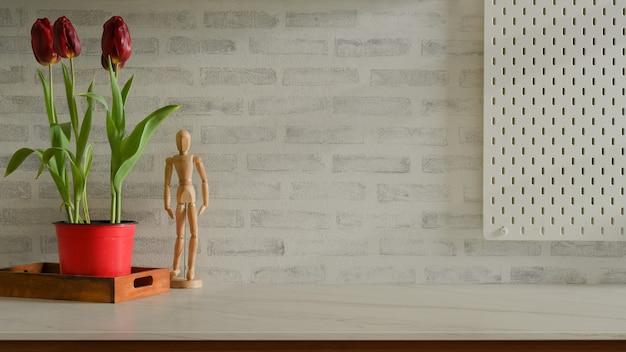 Przycięte zdjęcie marmurowego biurka z tulipanami, drewnianą figurą i przestrzenią do kopiowania w salonie