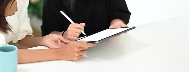 Przycięte zdjęcie matki pomagającej córce odrabiania lekcji online na cyfrowym tablecie w domu. edukacja online, nauka w domu.