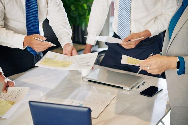 Przycięte zdjęcie menedżerów finansowych omawiających wpływ ekonomiczny pandemii covid-19 na firmę
