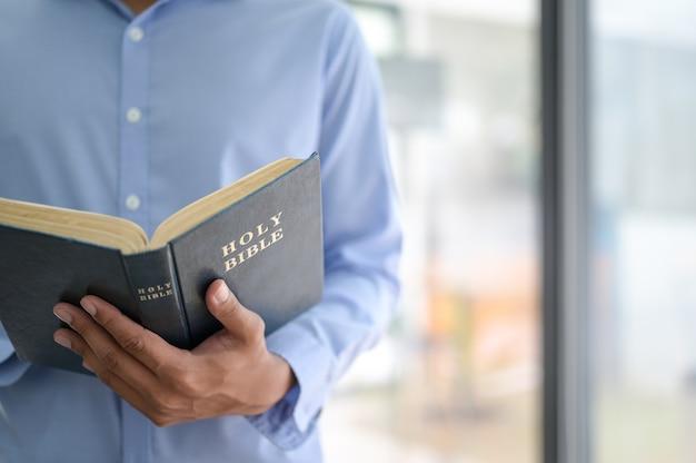 Przycięte zdjęcie mężczyzny trzymającego biblię w ręku