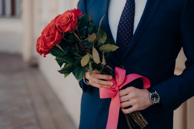 Przycięte zdjęcie mężczyzny ubranego w klasyczny garnitur, noszącego niebieski krawat i białą koszulę, z drogim zegarkiem na nadgarstku, trzymającego bukiet czerwonych róż ze wstążką, stojącego samotnie obok budynku