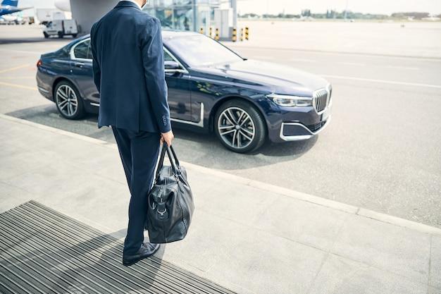 Przycięte zdjęcie mężczyzny w garniturze idącego ze skórzaną torbą z lotniska. czarny samochód przed nim