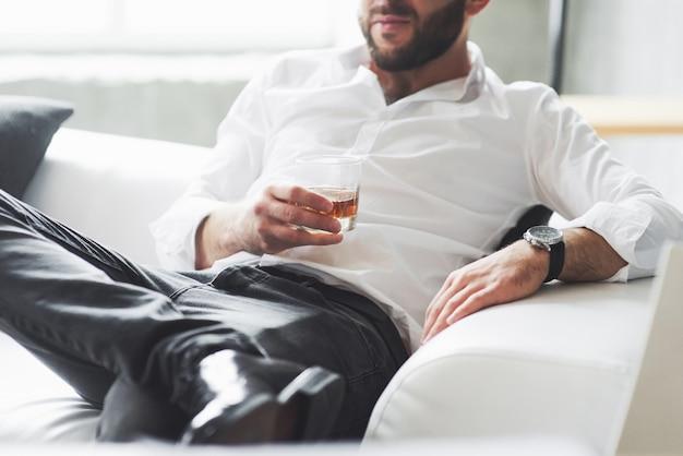 Przycięte zdjęcie młodego biznesmena w klasycznym stroju siedzącego na kanapie ze szklanką whisky w dłoni