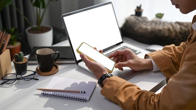 Przycięte zdjęcie młodego człowieka freelancera pracy z laptopem i przy użyciu telefonu komórkowego w nowoczesnym domu.