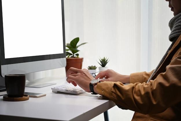 Przycięte zdjęcie młodego człowieka, patrząc na ekran komputera i pracy nad projektem w nowoczesnym biurze.