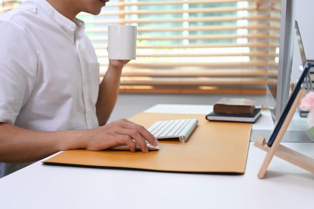 Przycięte zdjęcie młodego mężczyzny trzymającego filiżankę kawy i pracy online w domowym biurze.