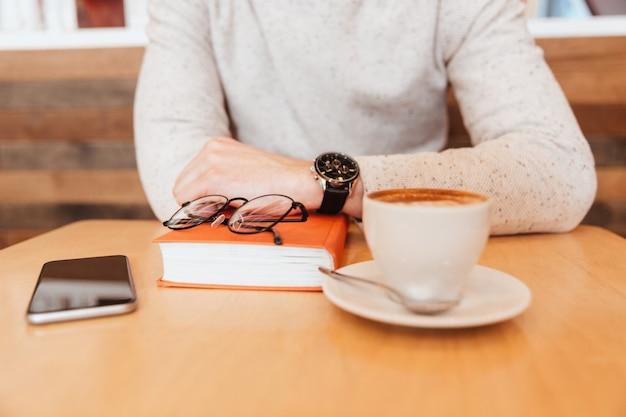 Przycięte zdjęcie młodego mężczyzny ubranego w koszulę, siedzącego w kawiarni z filiżanką kawy i książki.