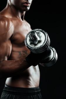 Przycięte zdjęcie młodego sportowca afroamerican, podnoszącego hantle