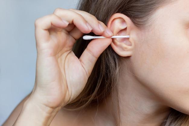 Przycięte zdjęcie młodej kobiety czyszczącej ucho wacikiem na białym tle na szarym tle