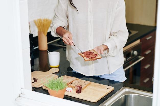 Przycięte zdjęcie młodej kobiety dokonywanie kanapki galaretki na śniadanie przy użyciu pełnoziarnistego chleba