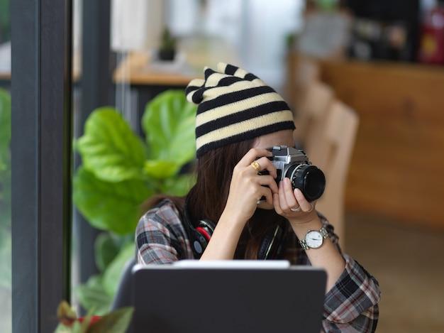 Przycięte zdjęcie młodej kobiety fotograf robienia zdjęć w obszarze roboczym