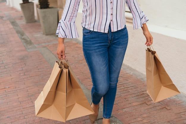 Przycięte zdjęcie młodej kobiety idącej ulicą z wieloma torbami na zakupy w dłoniach.