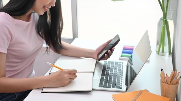 Przycięte zdjęcie młodej kobiety kreatywne pisanie na notebooku i czytanie w smartfonie.