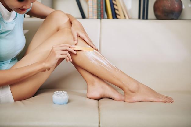 Przycięte zdjęcie młodej kobiety używającej szpatułki podczas nakładania kremu do usuwania włosów na nogi