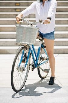 Przycięte zdjęcie młodej kobiety w dżinsowych szortach siedzi na rowerze z dużym przednim koszem