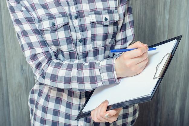Przycięte zdjęcie młodej kobiety w kraciastej koszuli, trzymając schowek i coś na nim pisze
