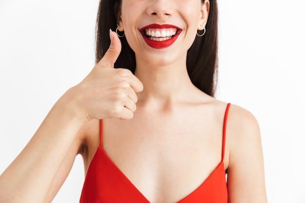Przycięte zdjęcie młodej pięknej kobiety ładnej pozowanie na białym tle pokazując kciuk do góry.