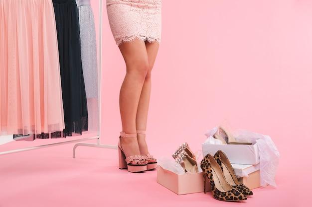 Przycięte zdjęcie młodej pięknej kobiety stojącej w pobliżu pudełek z butami i wieszakiem na ubrania z sukienkami, odizolowane na różowej ścianie