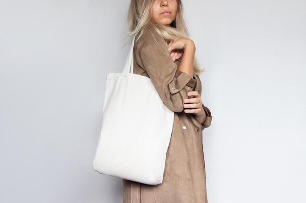 Przycięte zdjęcie młodej szczupłej kobiety w brązowym płaszczu z ekologiczną lnianą torbą z miejscem na tekst