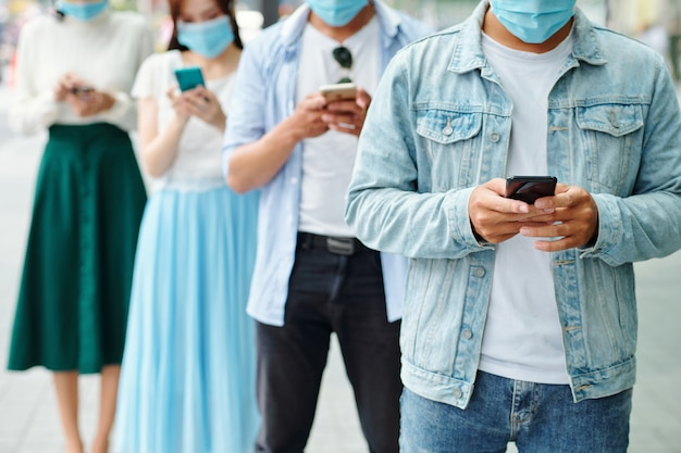 Przycięte zdjęcie młodych ludzi w maskach medycznych stojących jeden za drugim i wysyłających sms-y lub sprawdzających media społecznościowe zamiast komunikowania się