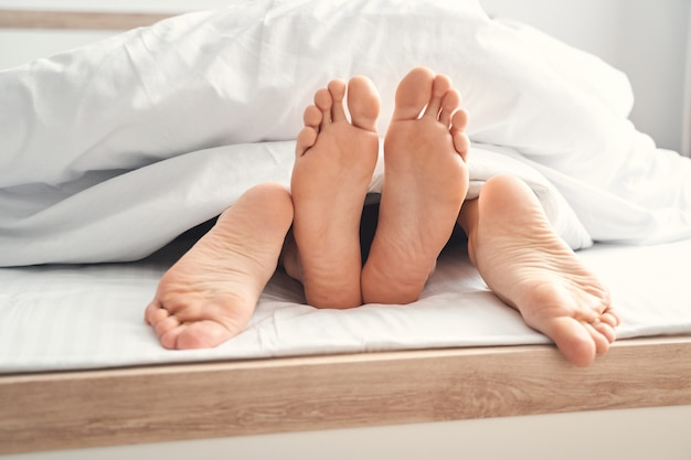 Przycięte zdjęcie namiętnego mężczyzny rasy kaukaskiej i młodej kobiety kochających się w łóżku